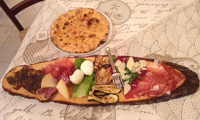 Un tagliere con salumi, formaggi, verdure grigliate e insalata