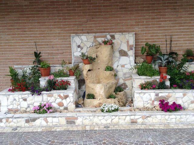 Dei muretti in pietra con dei vasi di fiori, delle piante interrate e al centro una pietra a forma di tronco con sopra della piantine