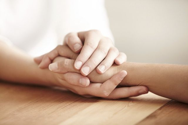 grieving holding hands