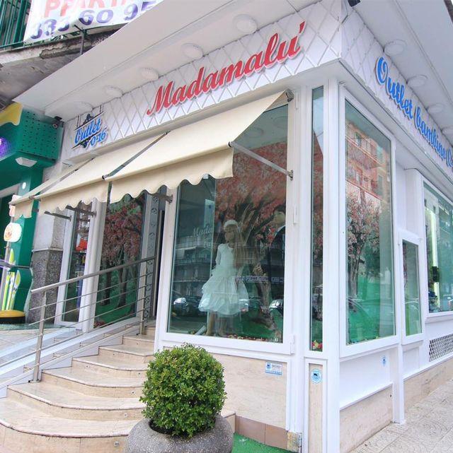 vista angolare di negozio MADAMALÙ con tenda da sole, boutique e scala esterna