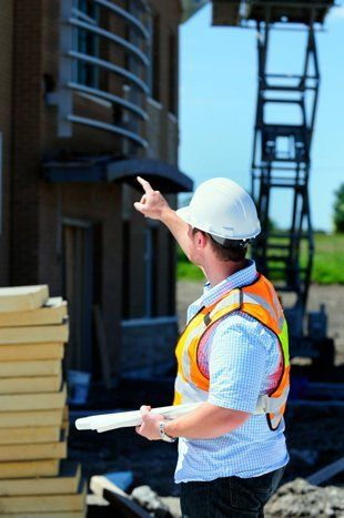 Man in hi-vis jacket pointing towards builing