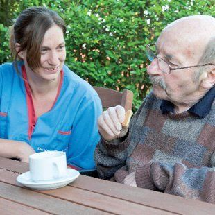 Nurse and elderly man having a cup of tea