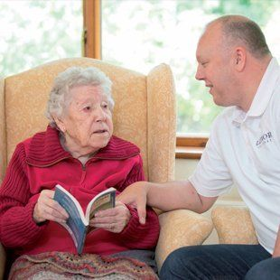 Male nurse reading with elderly woman