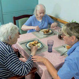 Elderly women eating with nurse