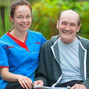 Carer with elderly man outside