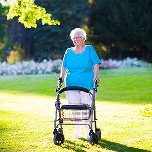 Elderly woman walking through gardens