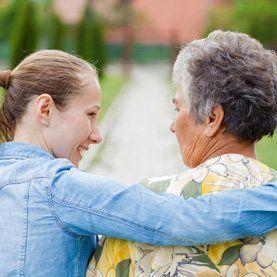Relative hugging elderly woman