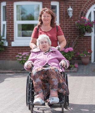 Woman pushing woman in wheelchair