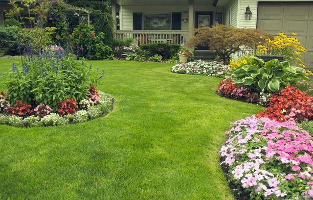 Un prato con tante aiuole di piante fiorite di vari colori davanti una villa Il tuo giardiniere VERDE VANTINI Colognola Ai Colli
