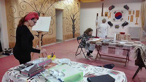 donna che dipinge una tela su un cavalletto