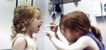 una bambina fa finta di visitare il cavo orale di un'altra bambina nello studio medico