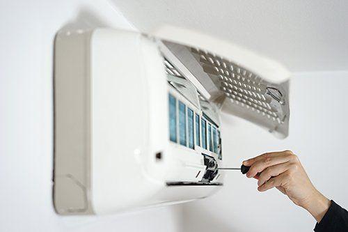 mano con cacciavite avvita un chiodo dentro un impianto di aria condizionata