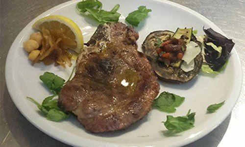 piatto a base di carne con basilico, ceci, limone, melanzane e pomodorini