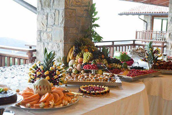 tavola imbandita con piatti di dolci e composizioni di frutta fresca
