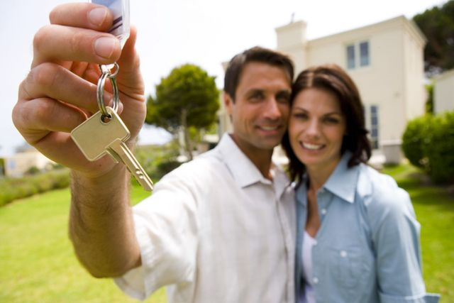 A couple holding keys in front of a home