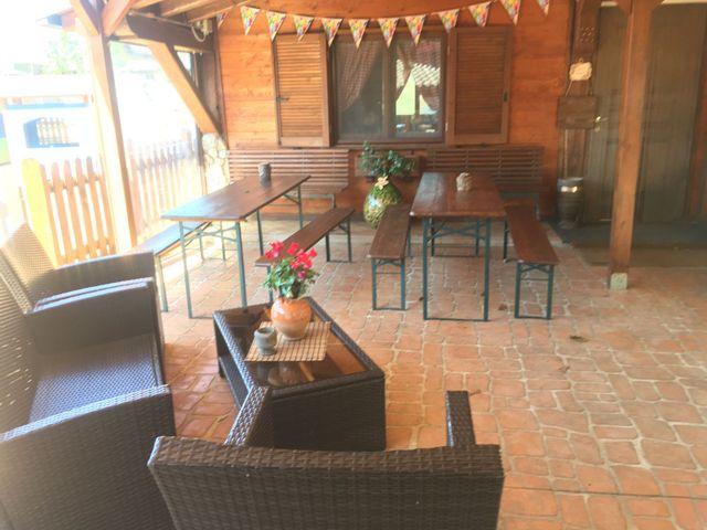 Tre tavoli con panche e sedie all'esterno di una casa