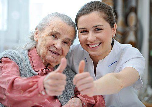 Badante e l'anziana felice mostrano il pollice in su a Varese