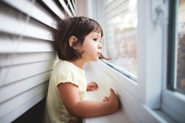 A kid peeping out of the window