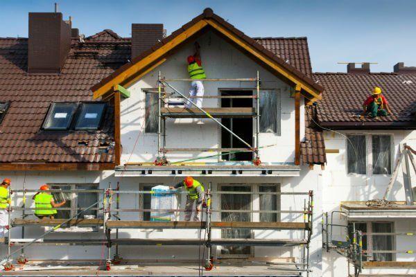 dei muratori al lavoro su un ponteggio durante una ristrutturazione di una villa