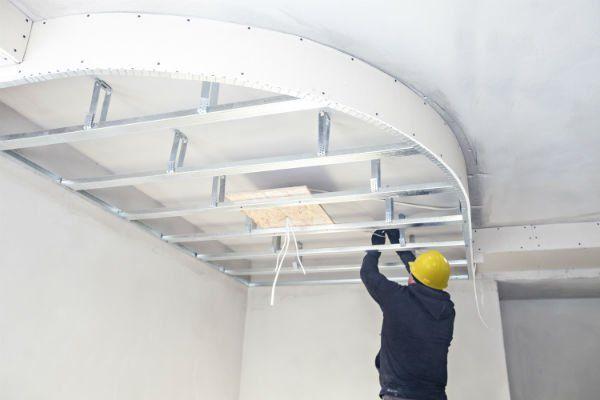 un operaio con un elmetto giallo al lavoro su un soffitto