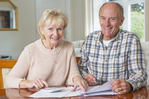 coppia di anziani con calcolatrice e fogli sulla scrivania sorridono guardando la macchina fotografica