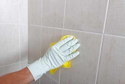 Cleaning bathroom tiles with cleaning products from our selection in Kirkcaldy