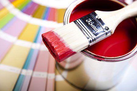 un pennello e un barattolo di vernice rossa