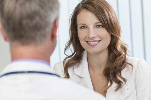 Happy smiling woman talking to her doctor