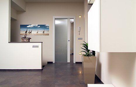 una stanza con sulla destra un vaso con una pianta, in fondo sulla sinistra un quadro appeso al muro e in centro una porta di vetro scorrevole
