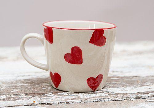 una tazza bianca a cuori rossi