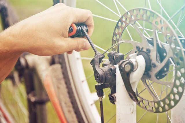 mano che ripara il cambio di una bicicletta