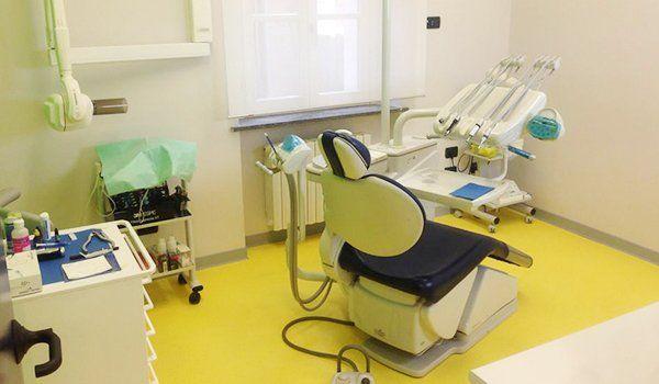 interno della sala del dentista con pavimento di color verde, lettino in pelle color blu e bianco, attrezzatura e carrello con sopra degli oggetti
