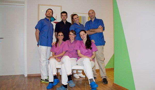 un gruppo di uomini e donne, alcuni in piedi vestiti di blu e altri seduti vestiti di rosa