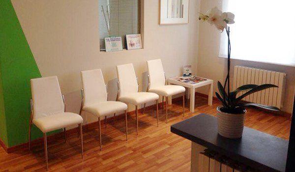 saletta d'attesa con quattro sedie color beige , un tavolino con sopra delle riviste e un pianale in legno scuro con sopra un vaso con un fiore bianco