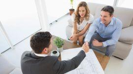 amminsitratore che stringe la mano all'inquilino, coppia seduta su divano tavolino con sopra un progetto