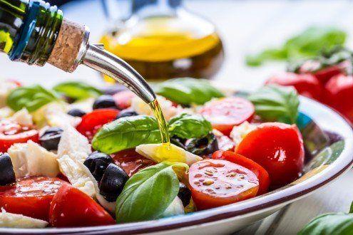 foto di una insalata di pomodori, olive nere, che viene condita con olio extravergine