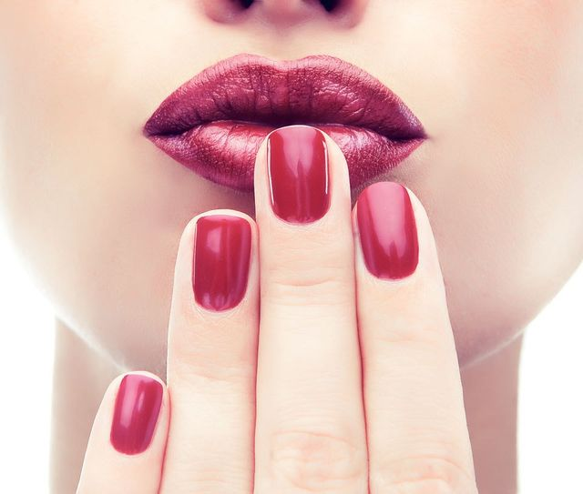 woman holding her red nails to her lips, spa concept