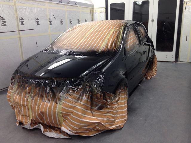a mechanic repairing the bumper of a car after a crash