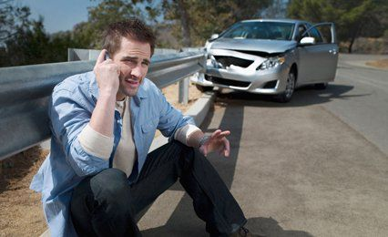 a man on the phone at the side of the raod after an accident