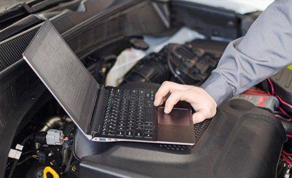 a mechanic testing the diagnostics of a car