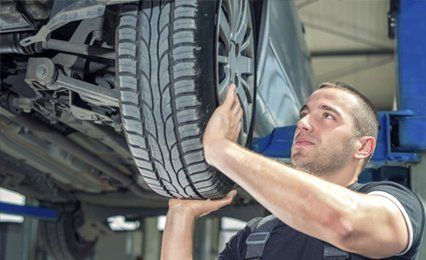 a mechanic fitting a tyre