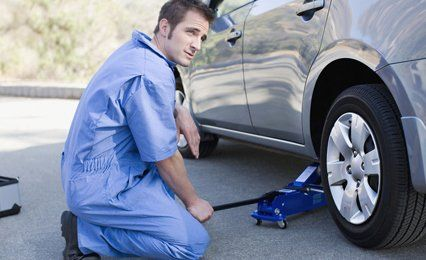 a mechanic jaking a car at the side of the road