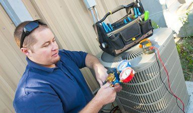 Air conditioner repair man using testing equipment on outside unit