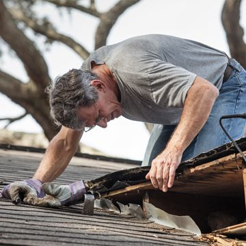 Man performs home inspection on roof