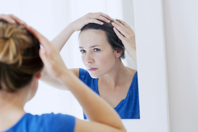 lady checking her hair in the mirror