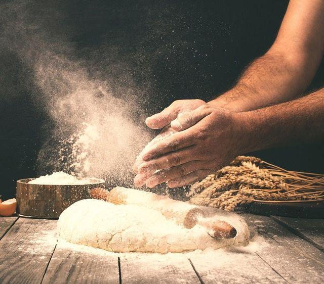 Uomo che prepara pasta di pane sul tavolo di legno in una panetteria vicino