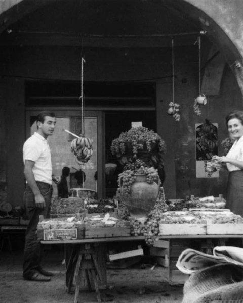 immagine in bianco e nero di due persone davanti a banchi di frutta e verdura