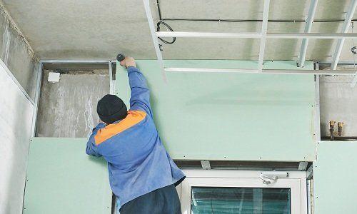 un uomo con una tuta blu e un cappellino di lana al lavoro su un soffitto