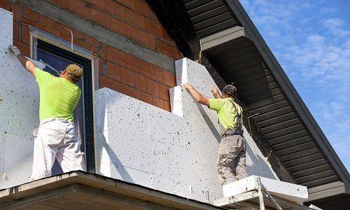 dei muratori su un ponteggio al lavoro su una facciata di una casa