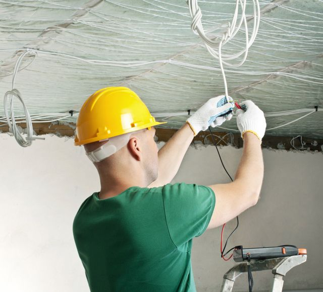 An electrician wires a ceiling light
